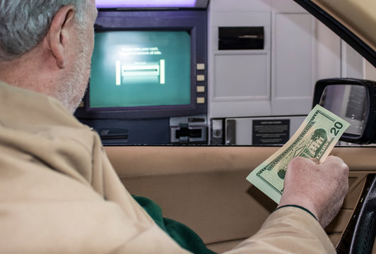 Senior man sitting in car with American dollars in his hand with bank ATM machine outside open window where he just made a transaction