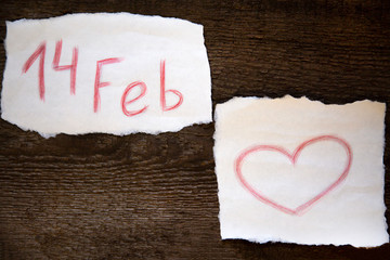 February 14 is written in red pencil on a piece of paper, the heart is drawn in red pencil on a piece of paper, everything is located on the old wooden board