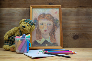 Children's drawing in a frame next to a teddy bear and a set of drawing