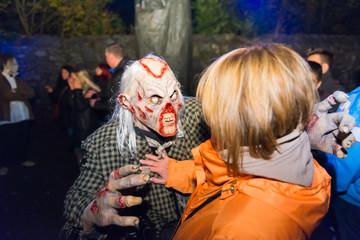 Halloween-Monster mit abgebissener, blutender Nase bedrängt Frau