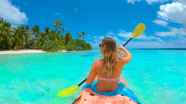 CLOSE UP: Young woman kayaking during her fun active vacation in Cook Islands.