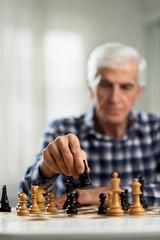 Close up of senior man playing chess at home