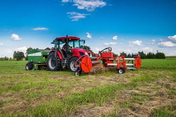 Fototapeta Nowoczesny traktor podczas zbioru siana. Baloty. Lato obraz