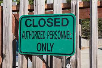 Green sign reading Closed Authorized Personnel Only posted on a fence.