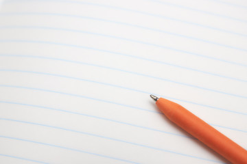 orange ballpoint pen lies on a white sheet of paper close-up. concept of education. place for text.