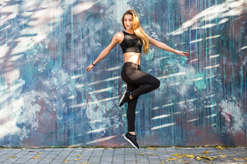 Young fitness woman in sportwear jump in front of street wall background. Outdoors