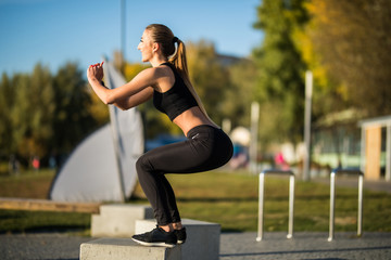 Young fitness woman in sportwear make workout exercise squats at city street.