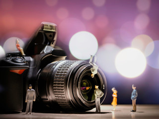 Professional DSLR camera and lens with bokeh background. Small human figures standing in front of the camera and lens