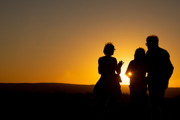 silhouette of a family on the beach at sunset