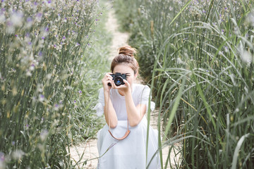 Woman with a camera the middle of the meadow with violet flowers Murdannia Giganteum in Prachinburi, Thailand. Photographer in nature.