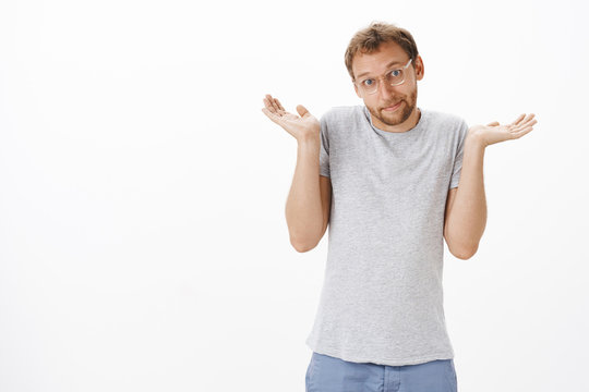 So what no big deal. Silly and cute caucasian adult bearded man in glasses and casual grey t-shirt shrugging with hands up smiling with sorry look being unaware and clueless over white wall