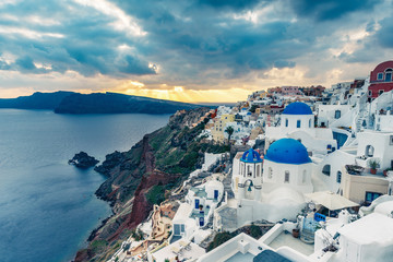 Churches in Oia, Santorini island in Greece, at sunset. Travel background.