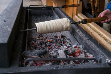 Kurtos kalacs (Chimney Cakes) baking on roll spinning over hot coals at a Christmas market stand.Chimney cakes baked over an open charcoal grill