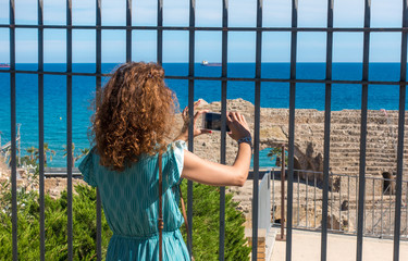 Girl taking a picture with a smartphone in Ancient roman amphitheater of Tarragona, Spain.The Archaeological Ensemble of Tarraco is declared a UNESCO World Heritage Site Ref 875