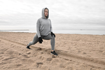 Isolated picture of athletic sporty girl in hoodie, leggings and sneakers warming up body, preparing leg muscles in crescent lunge pose on beach, having focused concentrated facial expression