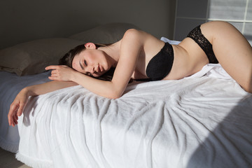 beautiful woman in underwear lies on the bed in the bedroom