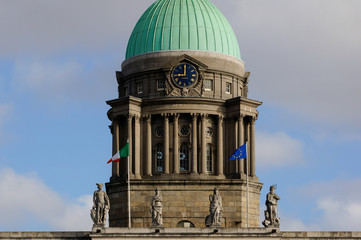 Closeup of The Custom House green dome in Dublin, Ireland.  Historical landmark from the 18th Century. Clock tower building decorated with coats of arms, heraldry and ornamental sculptures.