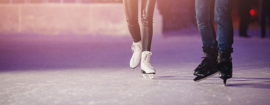 Closeup of winter skates on transparent ice rink night. Couple in love