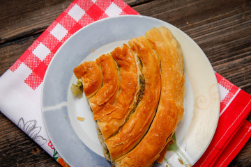Pastry with cheese and spinach and red dish towel on an retro style wooden table