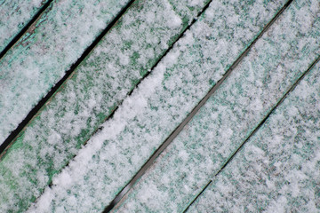Green textured surface covered with snow