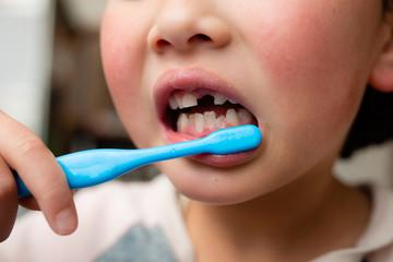 歯磨きをする前歯が抜けた子供
