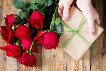 Mother day background or Valentines Day, wedding day. Beautiful blooming Red roses and present on wooden board. Top view flat lay background.