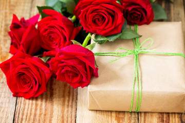 Mother day background or Valentines Day, wedding day. Beautiful blooming Red roses and present on wooden board.