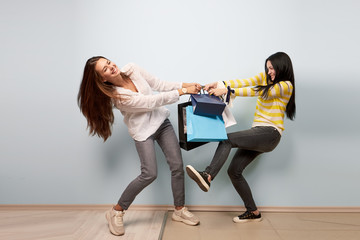 Two girls dressed in nice casual clothes pull and take each other shopping bags on the white background