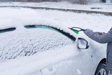 Зима. маленький мальчик чистит щеткой стекло автомобиля
