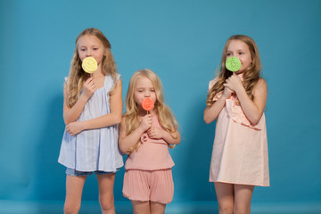 three little girls eat sweet candy lollipop