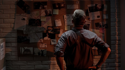 Policeman analyzing information of crime on investigation board, professional - fototapety na wymiar