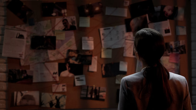 Lady private agent looking at crime investigation board, chasing serial killer