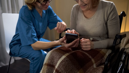 Nurse showing senior woman how to use cell phone, easy online shopping app