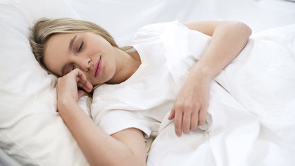 Satisfied woman sleeping in bed, relaxation time, resting after hard busy week