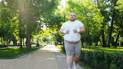 Fat young man jogging in park, obesity concept, struggling with insecurity