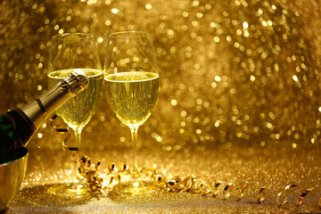 Obraz Kieliszki i butelka z szampanem na złotym, błyszczącym tle. - fototapety do salonu