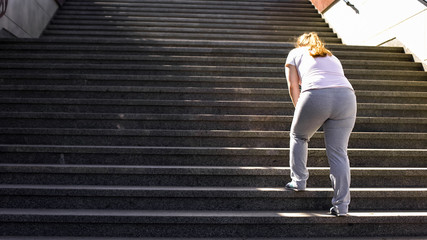 Hard to climb stairs for obese girl, victory over fatigue for goal achieving Fototapete