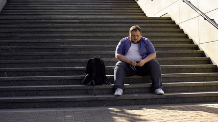 Fat man listening to music on stairs, loneliness, overweight causes insecurities