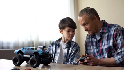 Father and son operating radio-controlled car, leisure activity, birthday gift