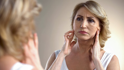 Unhappy aged woman looking in mirror at home, touching face, aging process
