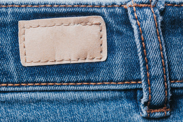 Blue denim jeans trousers background. Brown leather empty copy space label texture.