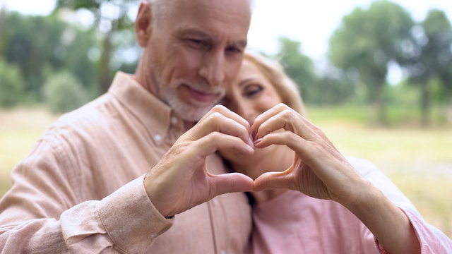 Romantic husband and wife showing heart gesture by hands, old age tenderness
