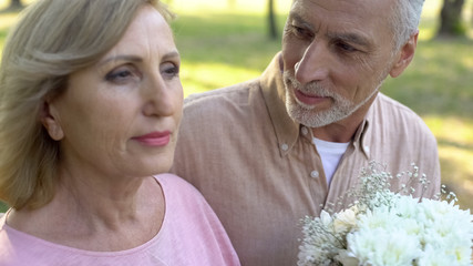 Gray-haired retired man with white flowers looking at attractive elderly woman