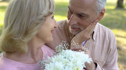 Senior man giving flowers to beloved woman, pleasant date surprise, anniversary