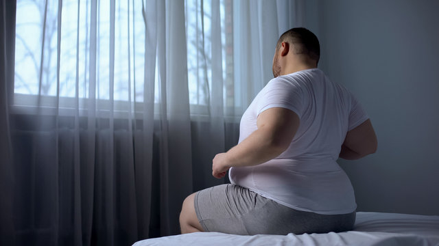 Hulking fat man stretching muscles in morning on bed, suffering from back pain