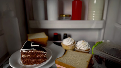 Pie, cupcakes and sandwiches inside fridge, concept of unhealthy nutrition
