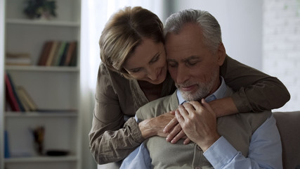 Retiree lady hugging man, loving relations in long marriage, closeness and care