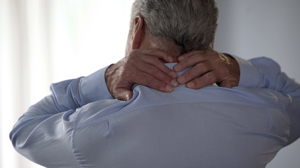 Retiree man rubbing back of his neck, standing backwards, office desk worker