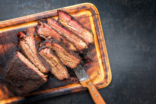 Traditional smoked barbecue wagyu beef brisket as piece and sliced offered as top view on an old cutting board with copy space right