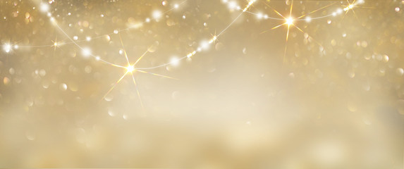 Christmas golden glowing background. Holiday abstract glitter defocused backdrop with blinking tars...
